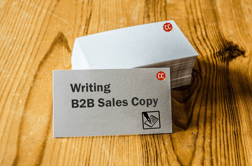The image shows a visiting card with writing B2B sales copy written on it